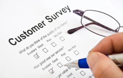 white hand holding pen filling out Customer Survey