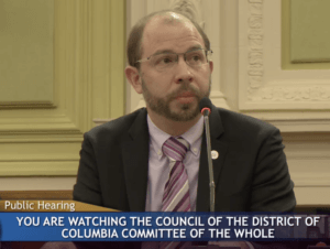 Eric Kaika (white male in dark grey suit, with light purple shirt and assorted color tie, TDI pin on suit lapel) sitting in front of a microphone preparing to testify at The Council of The District of Columbia Committee of the Whole on 12/11/2018