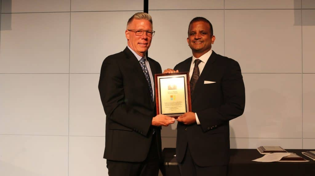 While male with salt and pepper hair and glasses wearing dark suit with tie holding a plaque with a person of color male with dark hair wearing dark suit and tie.