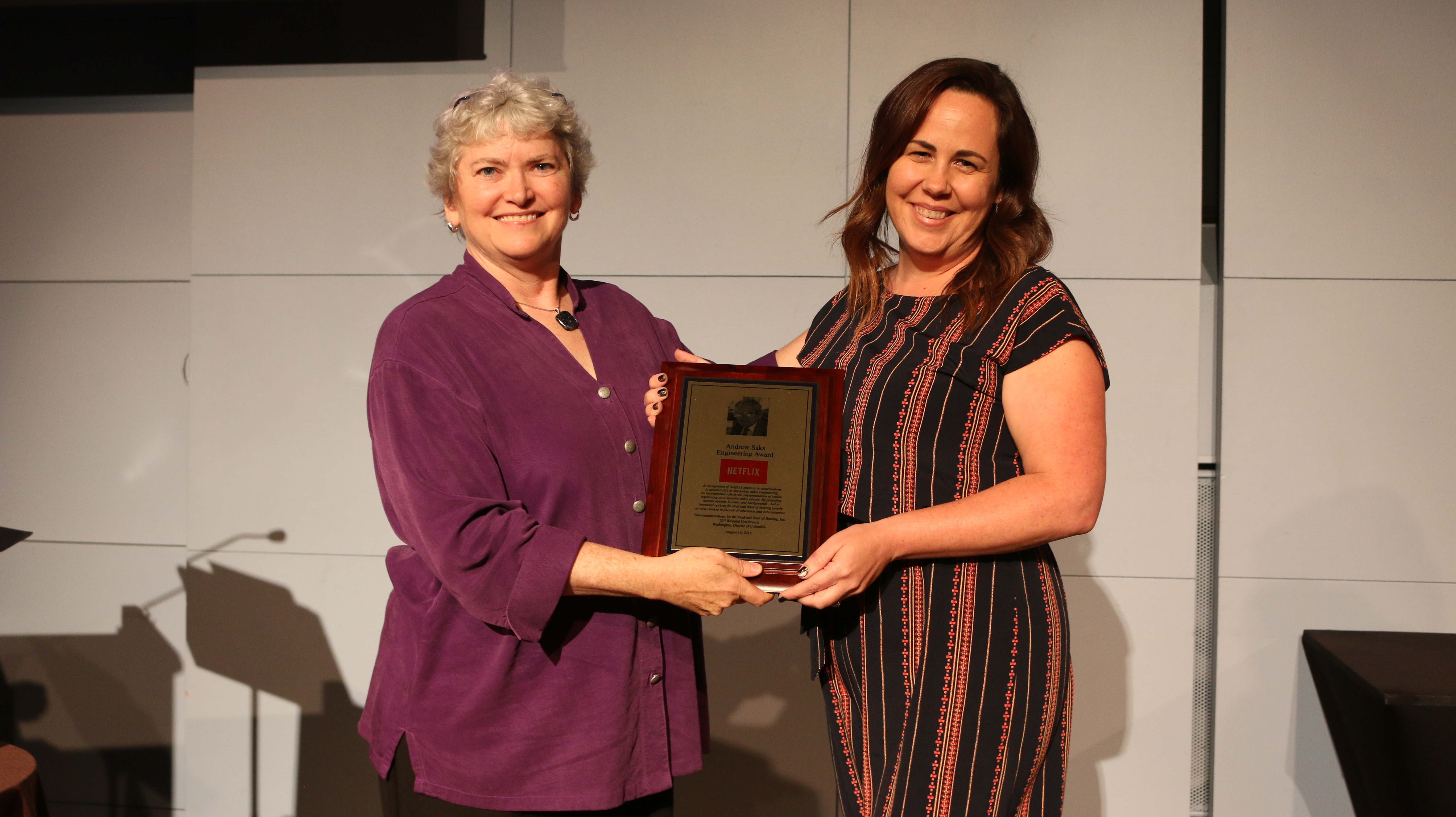 White female with salt and peppered hair wearing purple button down blouse holding a plaque with a white female wearing a vertical patterned dress