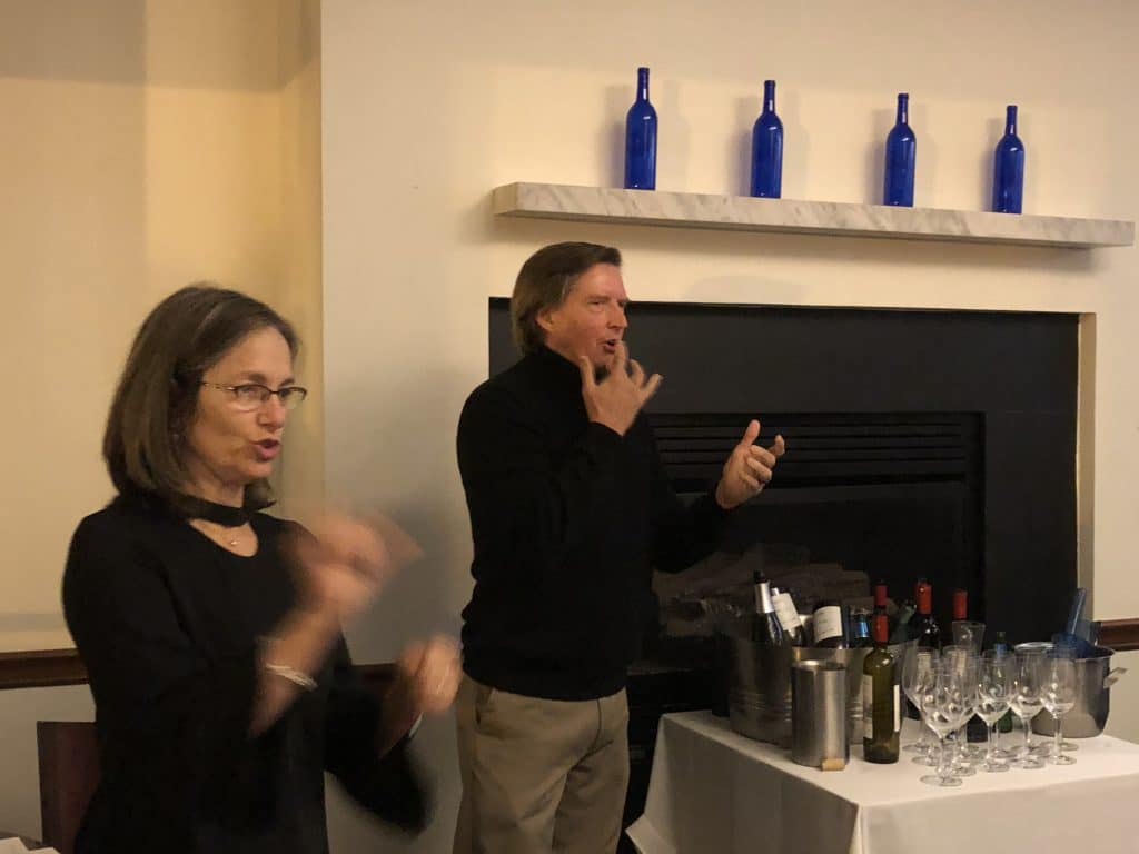White male with dark brown hair wearing dark sweater and tan slacks standing next to a table of wine bottles and glasses. On his right is an ASL Interpreter