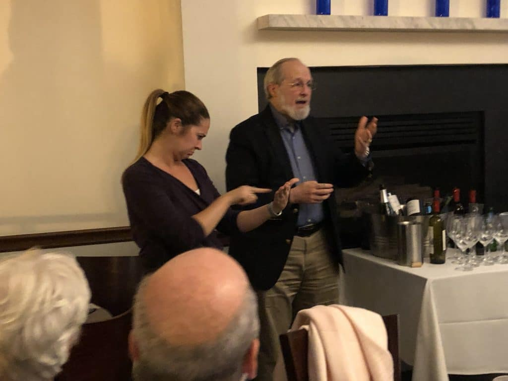 White male with salt and pepper hair with white beard, wearing dark jacket, blue button down shirt and tan slacks standing next to a table of wine bottles and glasses. On his right is an ASL Interpreter